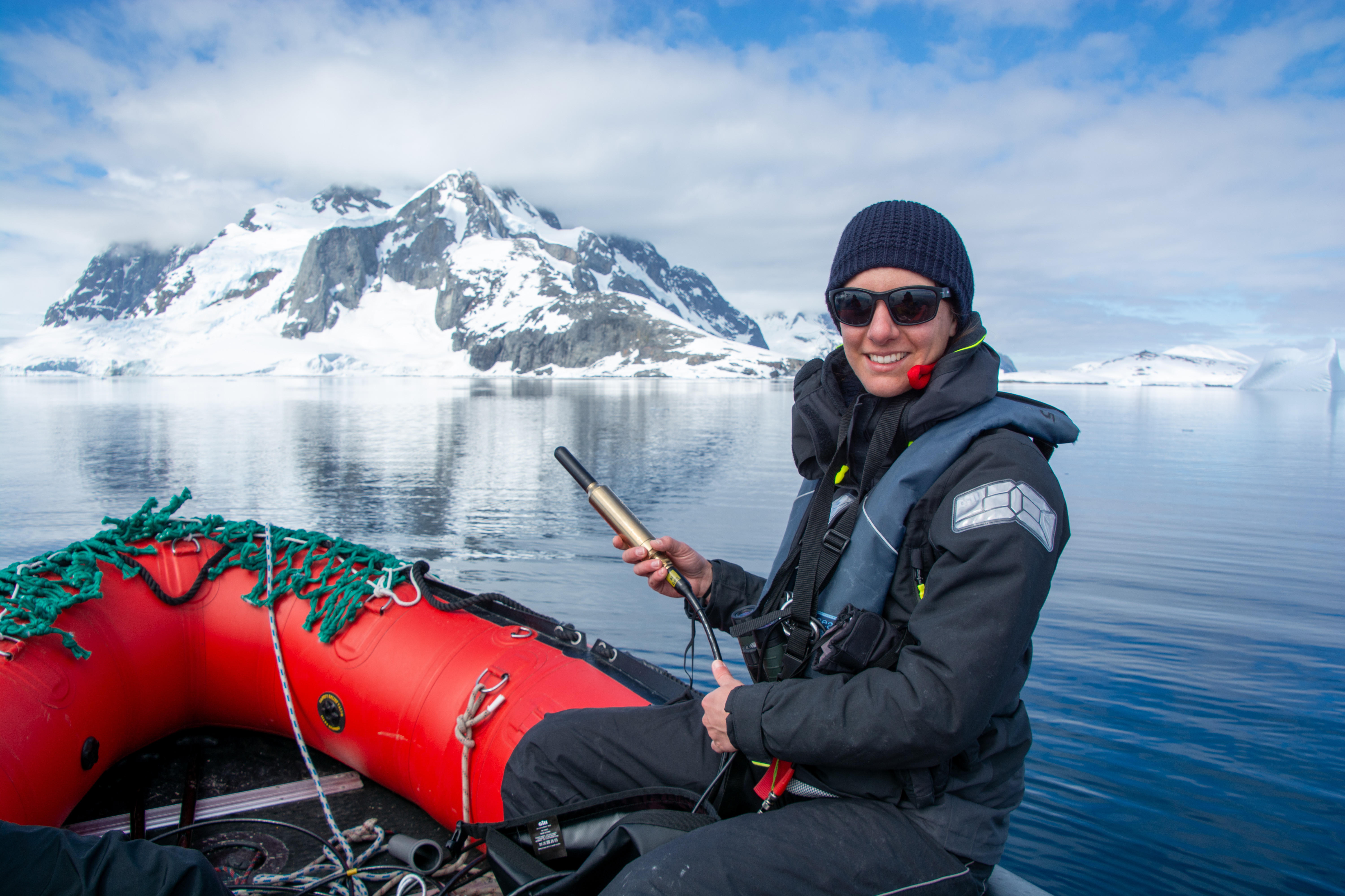 Helen on the dinghy in the Southern Ocean. She holds a hydrophone in her hand. Photo: Caesar Schinas.